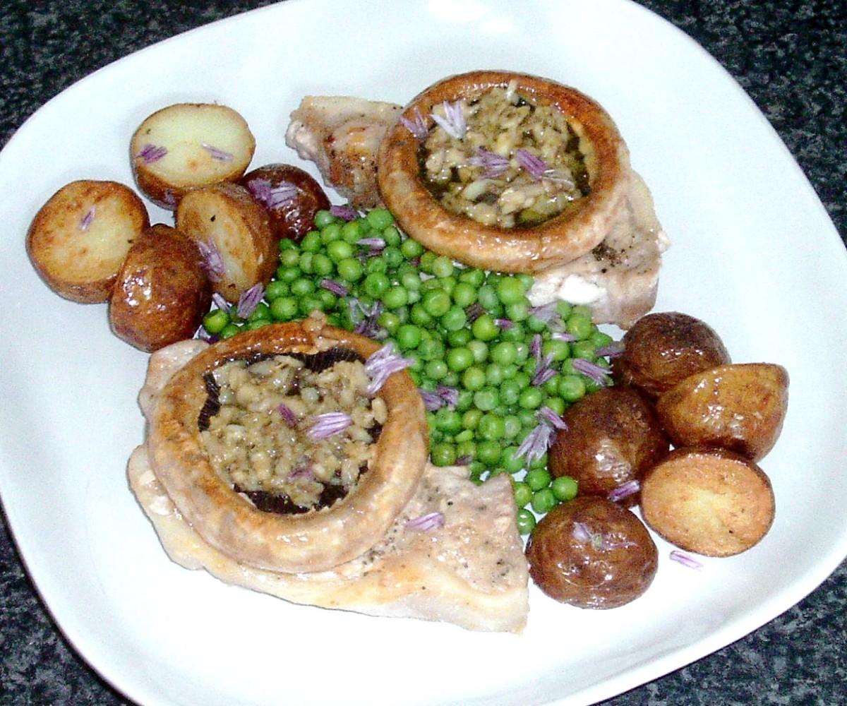 Stuffed garlic mushrooms on pork loin fillets with deep fried potatoes and peas