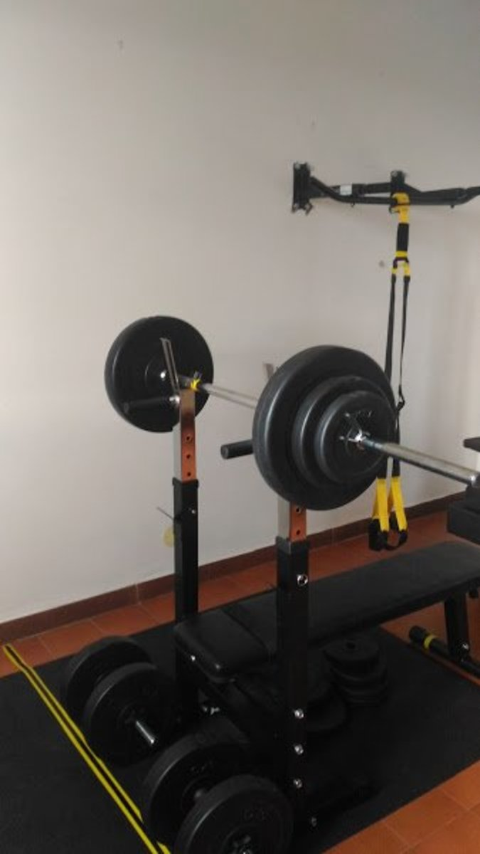 A loaded barbell on a bench; a traction bar with suspension trainers.