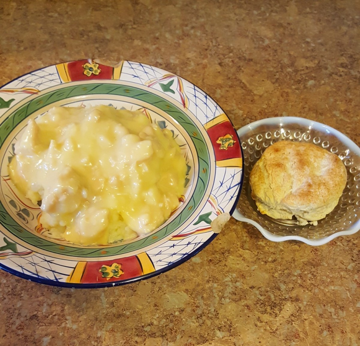 Chicken gravy over mashed potatoes, served with a biscuit.