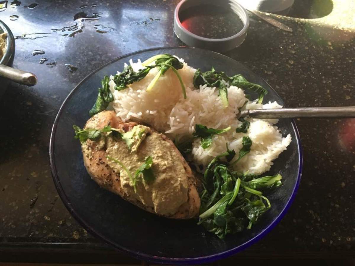 A finished chicken breast with sauce spread over it along with rice and spinach.