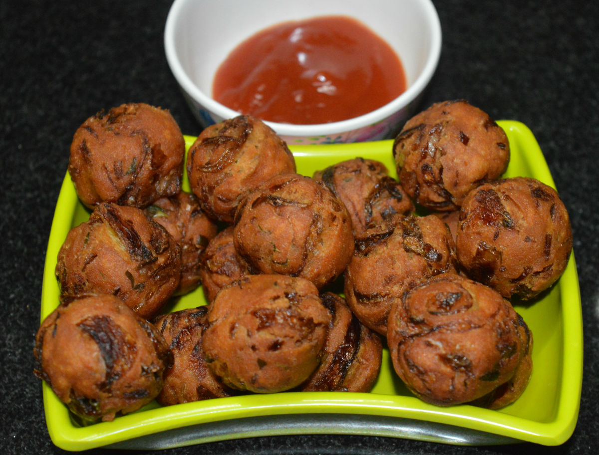 Hot onion bondas or pakoras served with tomato sauce.