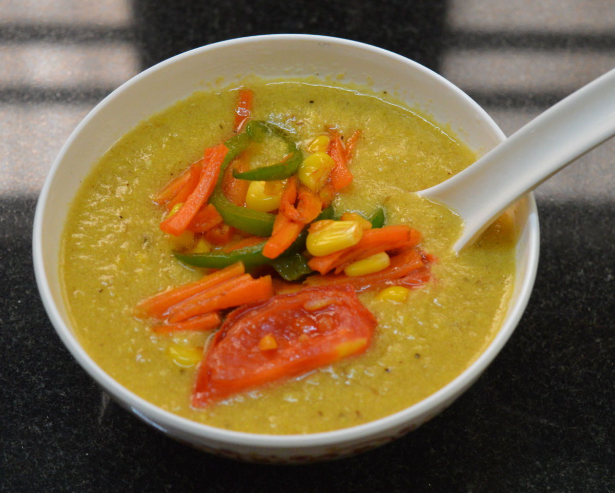 Corn soup topped with sauteed vegetables.