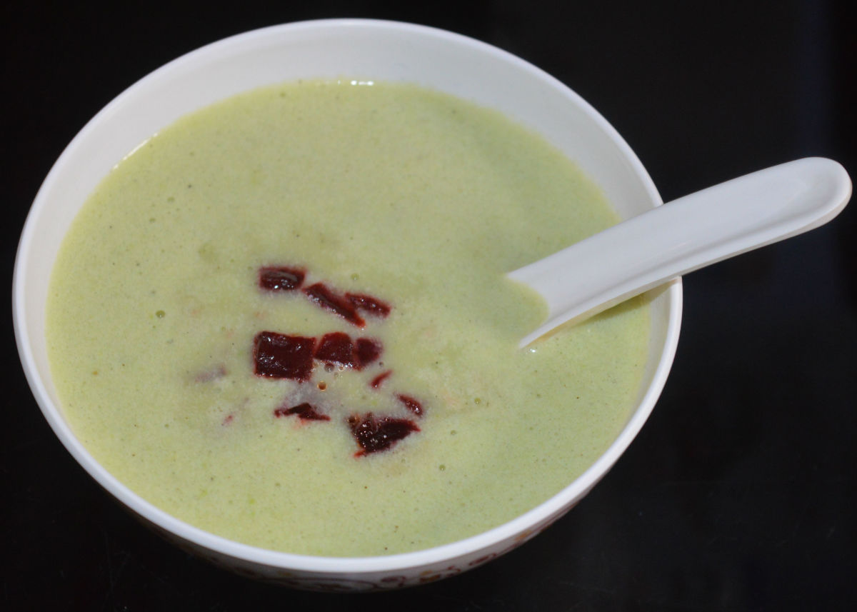 Green pea and potato soup with beetroot topping.