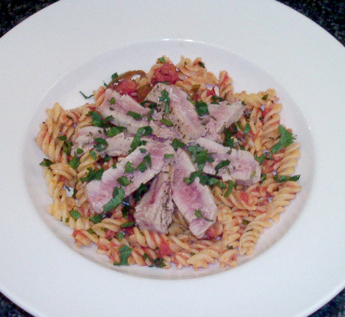 Tuna loin fillet is seared, sliced and served on a bed of fusilli pasta in a spicy tomato sauce