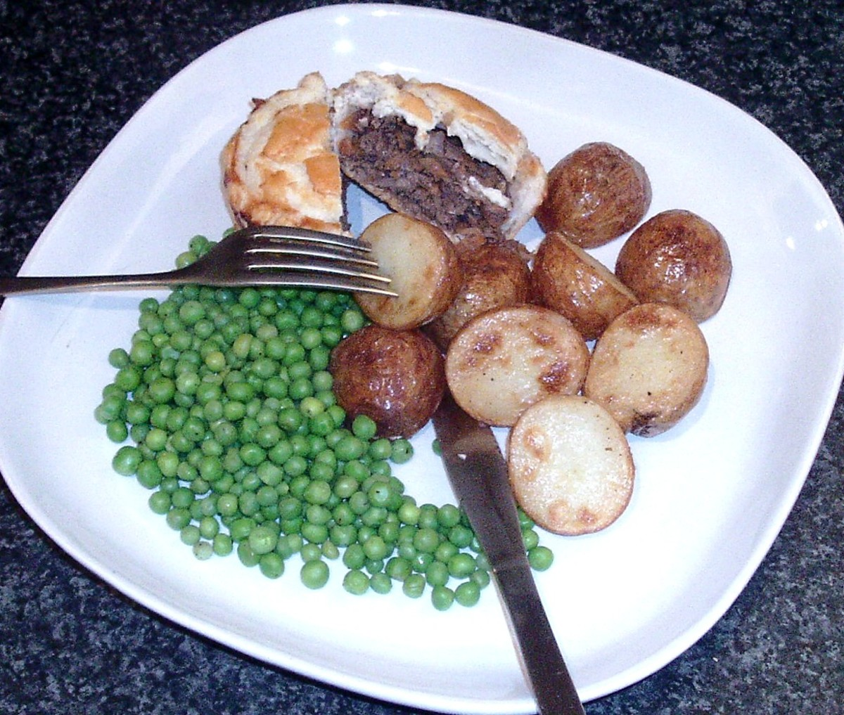 Venison and red wine gravy mini puff pastry pie with roast potatoes and peas