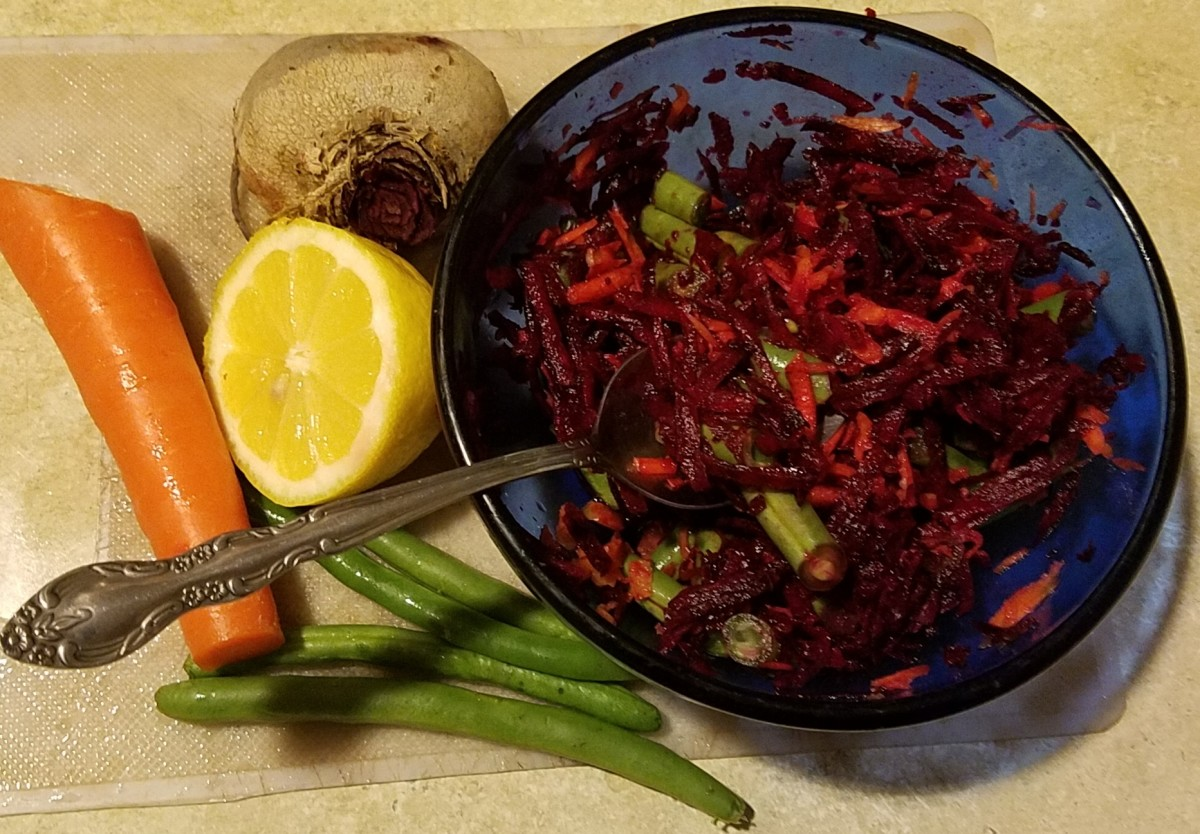 A deliciously colorful beet salad posed for this photograph alongside some of the ingredients that gave themselves to its creation.
