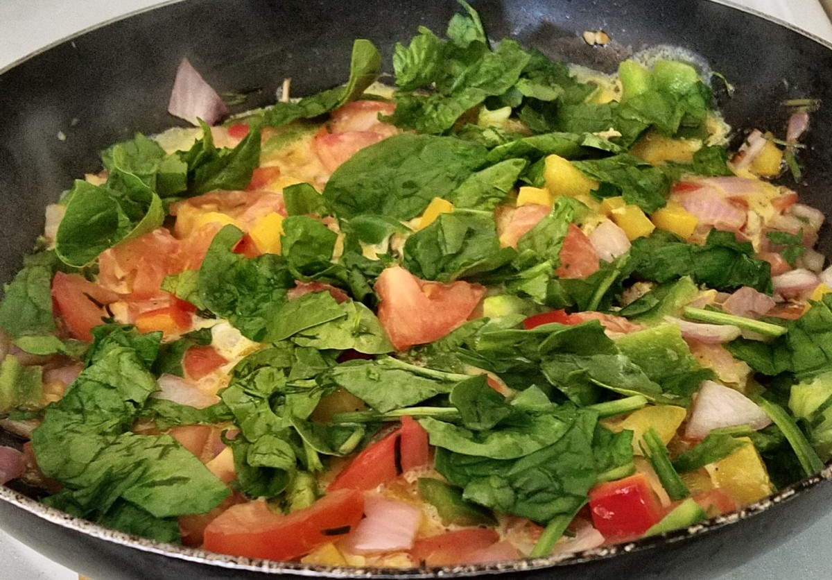A colorful garden veggie omelet sizzles in the pan, almost done.