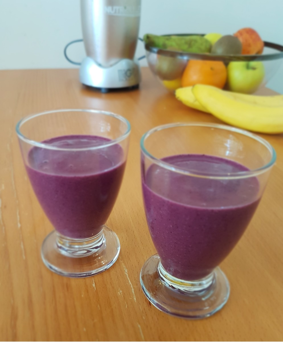 A couple of small blueberry banana smoothies ready to drink.