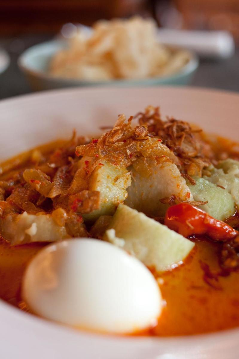 """Rice cakes in coconut and vegetable sauce served for breakfast with fried shallots and prawn crackers. Also known as """"lontong sayur."""""""