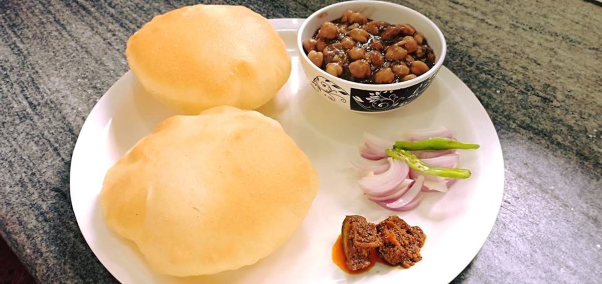 Instant bhature served with pindi chole, mango pickle, sliced onions, and green chillies