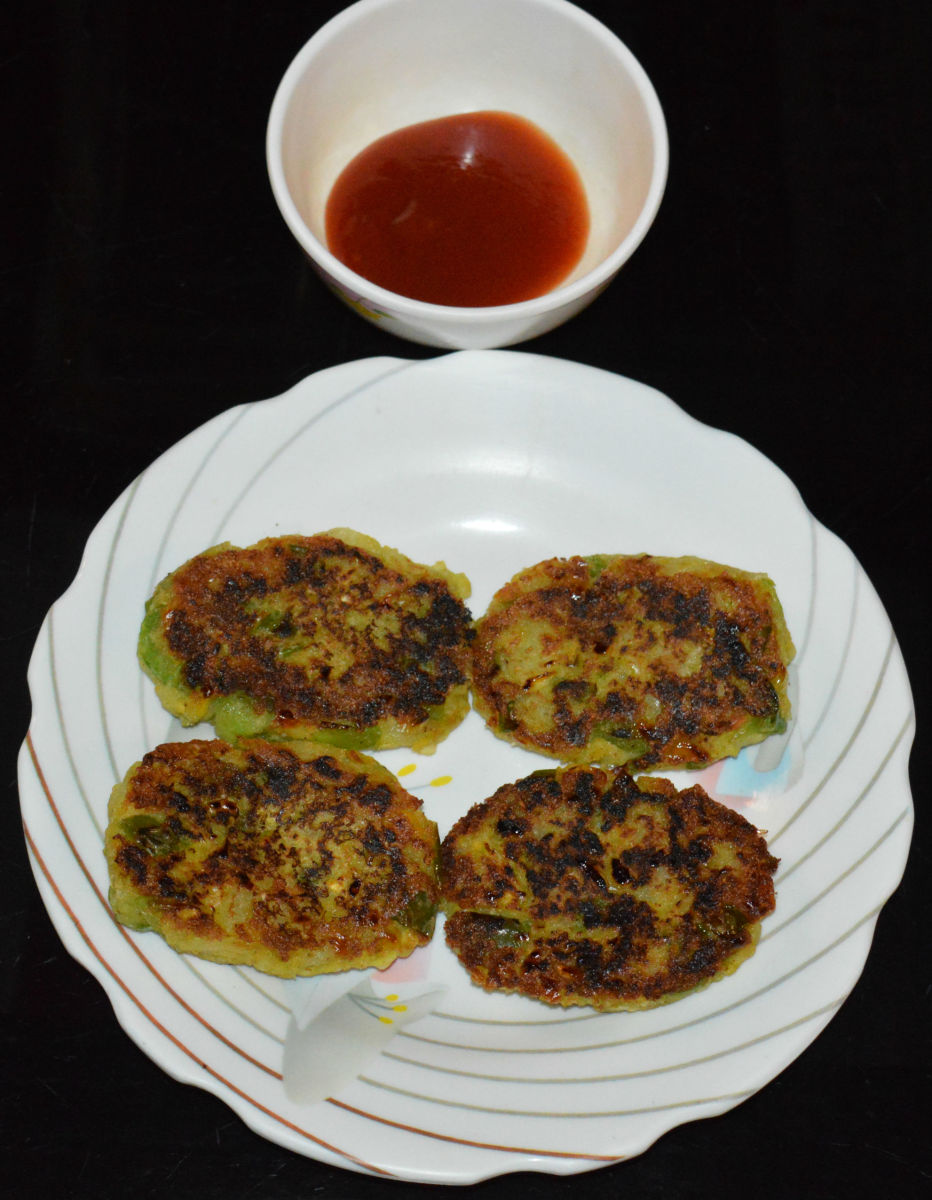 The finished corn capsicum cutlets served with tomato sauce.