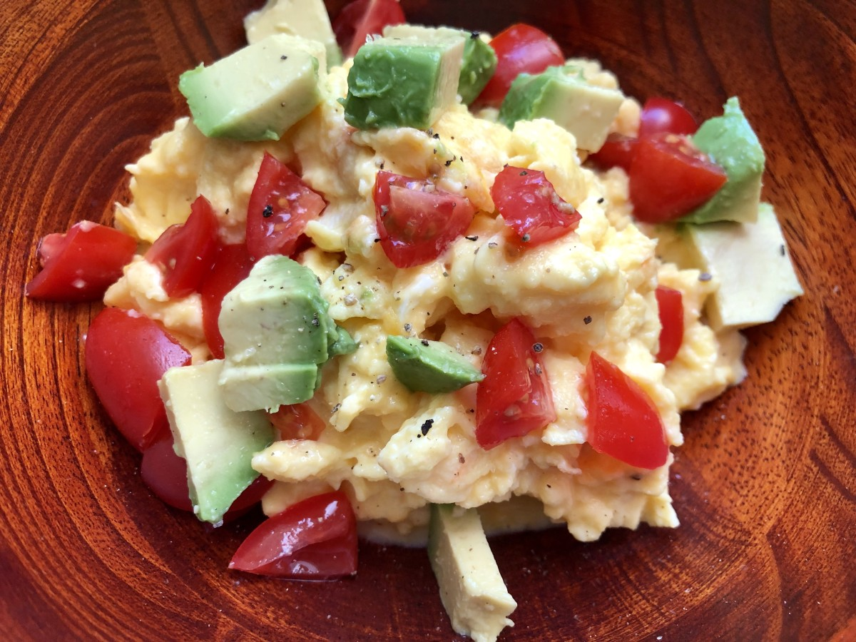 Topped with fresh tomatoes, avocado, salt, and pepper, these scrambled eggs are delicious!