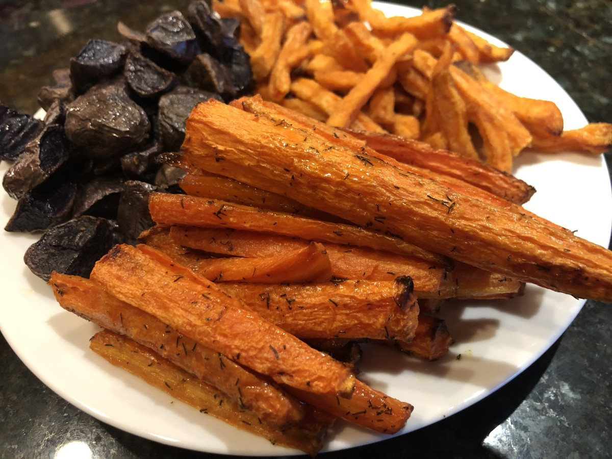 Roasted carrots (foreground), purple potatoes, and shoestring sweet potato fries