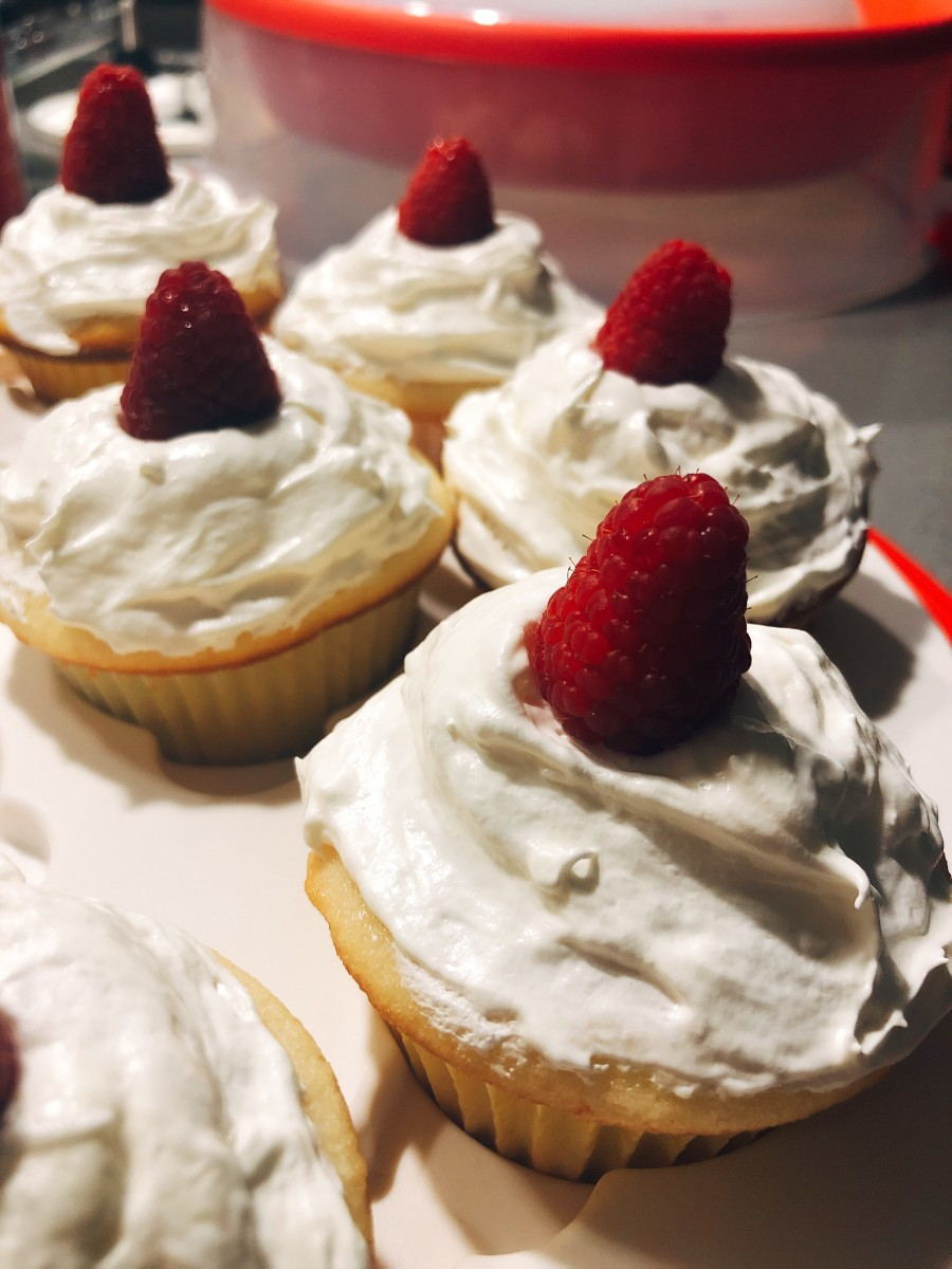 Vanilla cupcakes with vanilla frosting and fresh raspberries. Yummy!