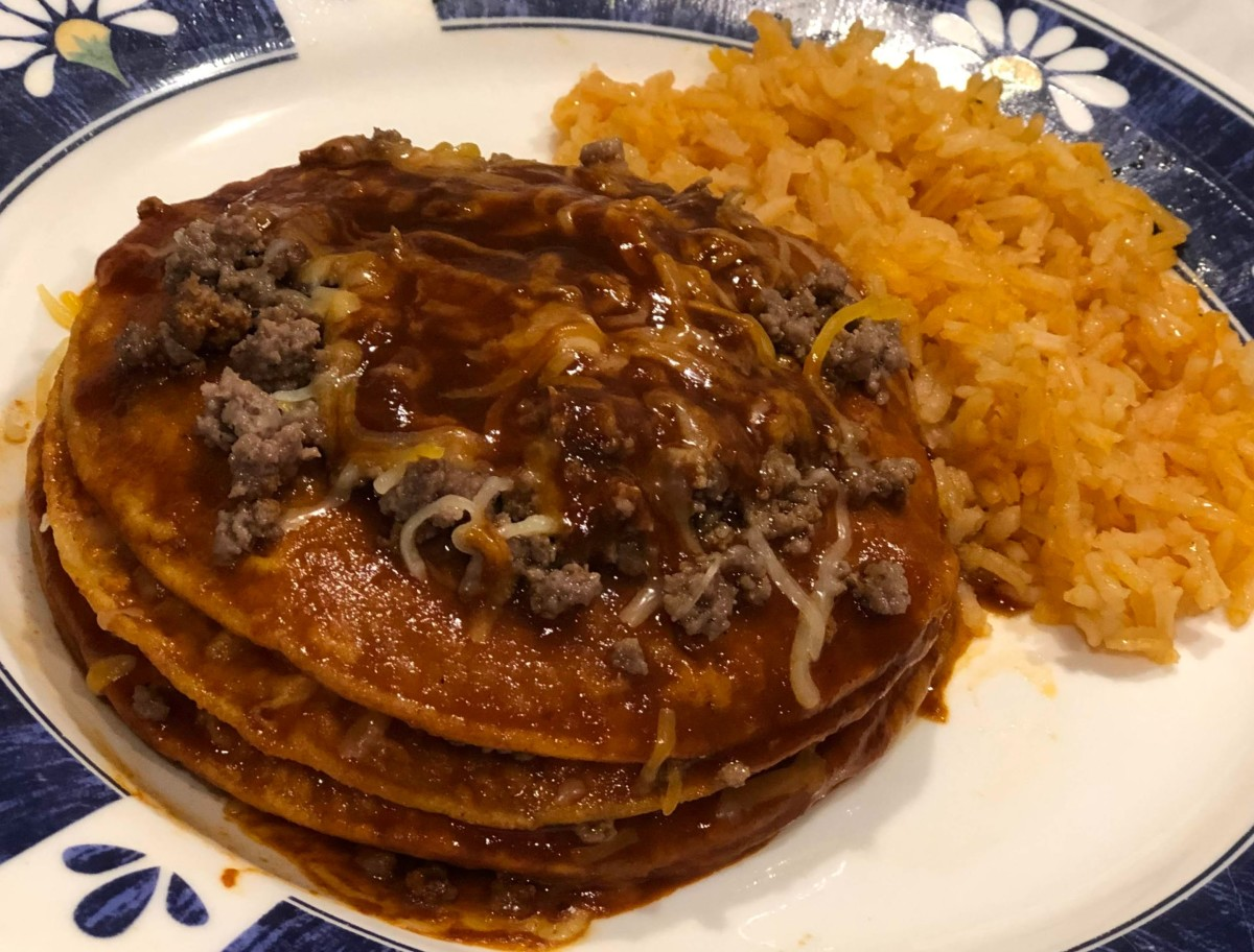 Red Tex-Mex enchiladas with a side of Mexican-style rice.