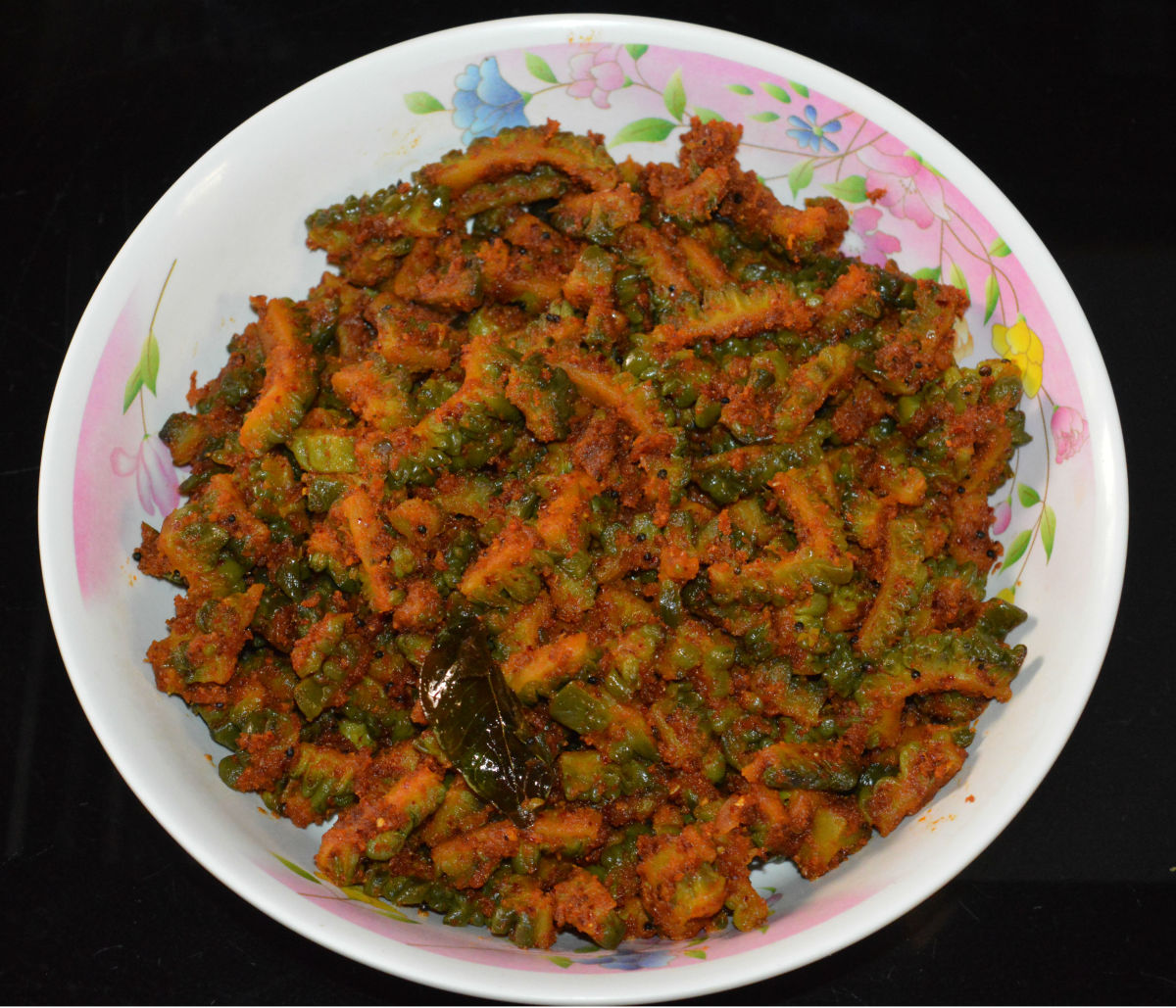 A bowl of spicy bitter gourd curry with peanut masala.