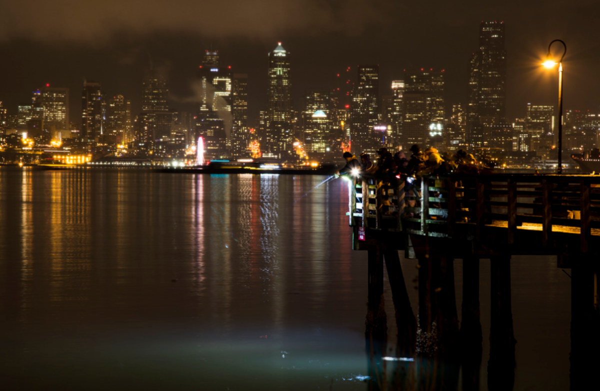 Squid fishermen at night in West Seattle. Notice the bright lights they use to illuminate the water to attract squid.