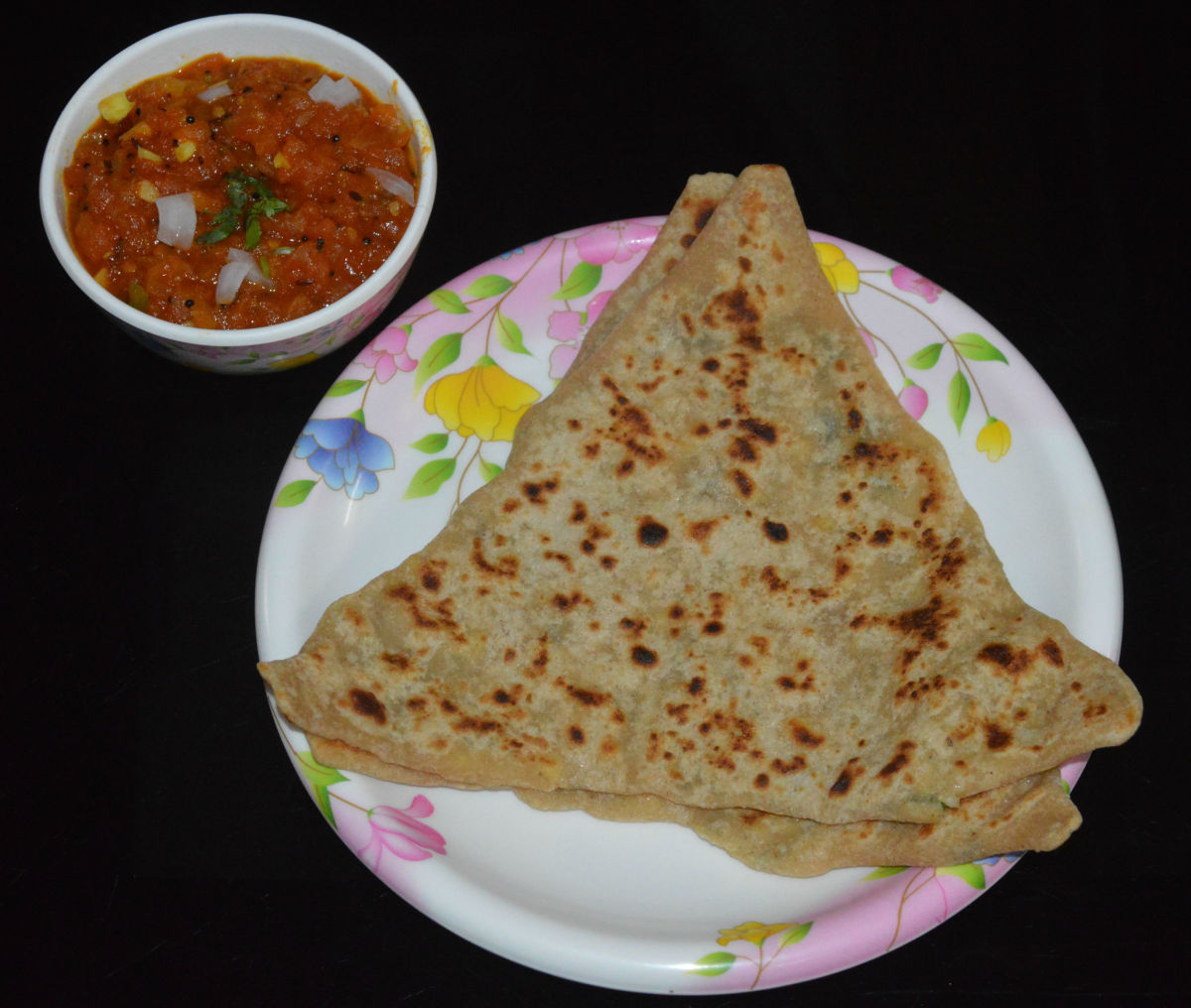 Paneer paratha served with homemade tomato salsa