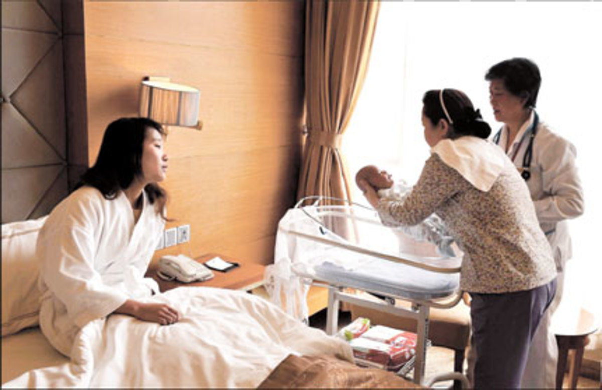 A woman watches a nanny care for her newborn baby as she continues her 30 day bed-rest during Sitting The Month