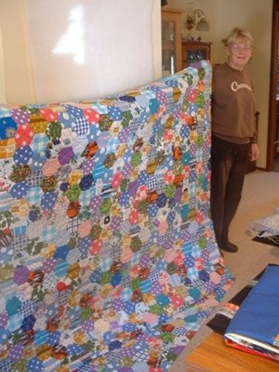Margaret (student) shows the hexagon quilt she completed from the many hexagons made by her mother from family scrap fabrics.