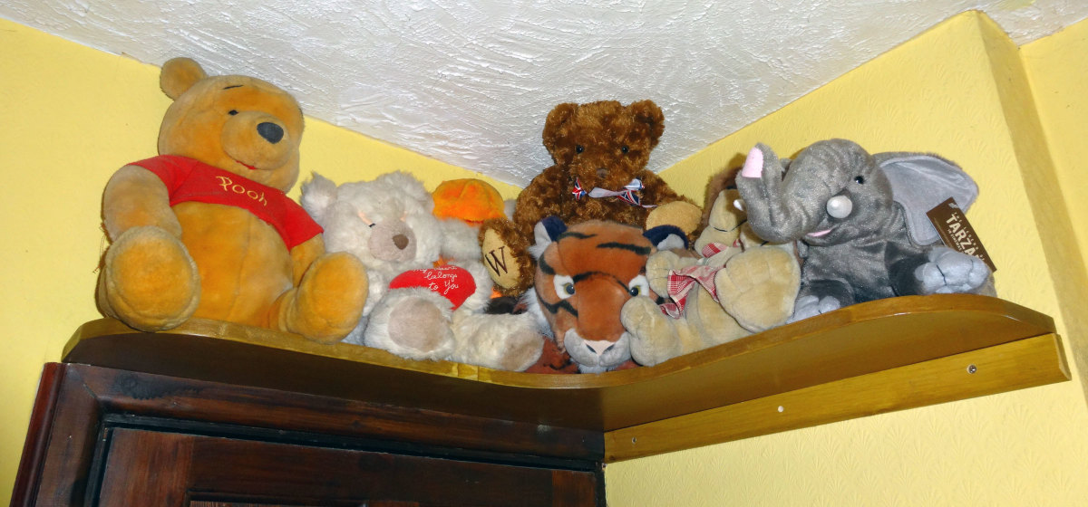 Soft cuddly toy animals displayed on shelf fitted above our bedroom door.