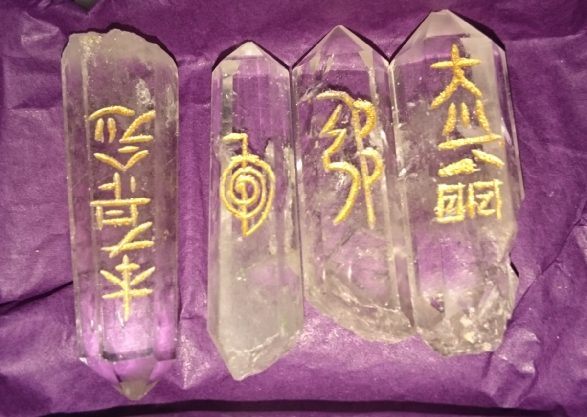 Quartz crystal points carved with reiki symbols.