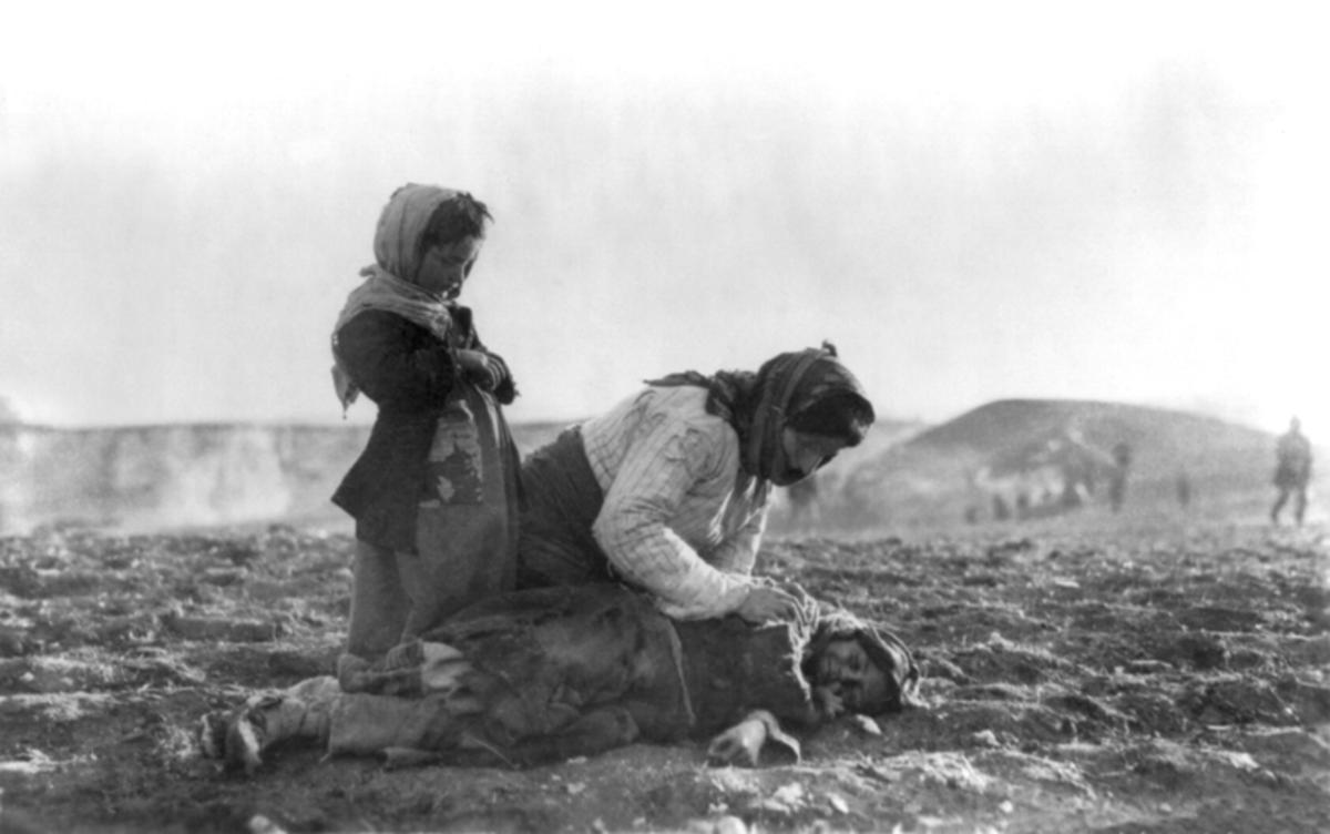 An Armenian woman kneels beside a dead child.