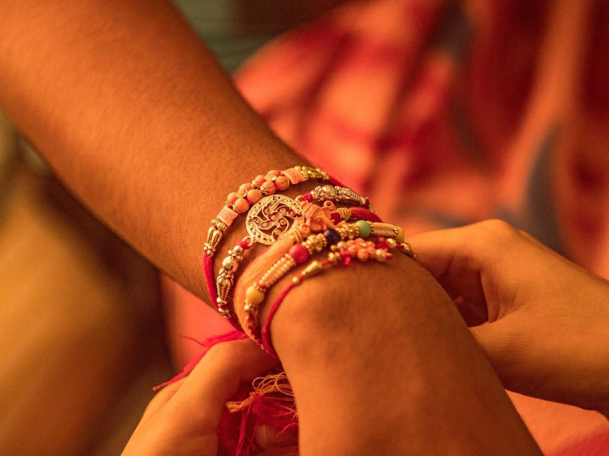 The sister ties a Rakhi on the wrist of the brother's hand.