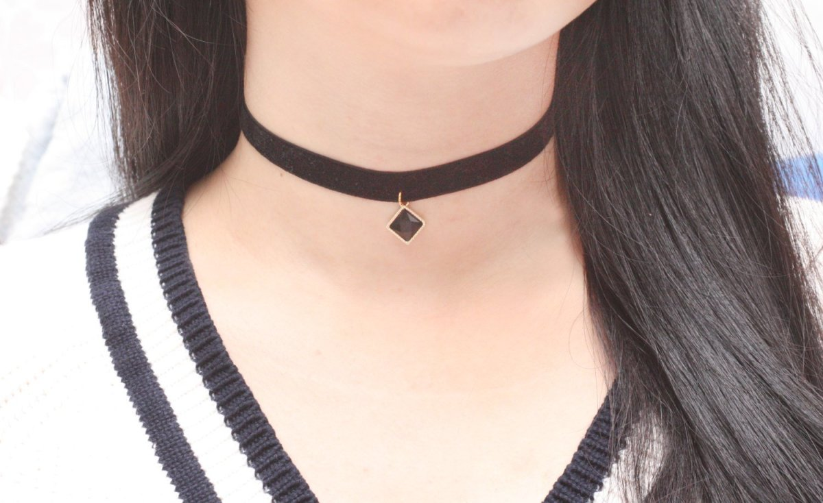 A black choker with a diamond shaped charm