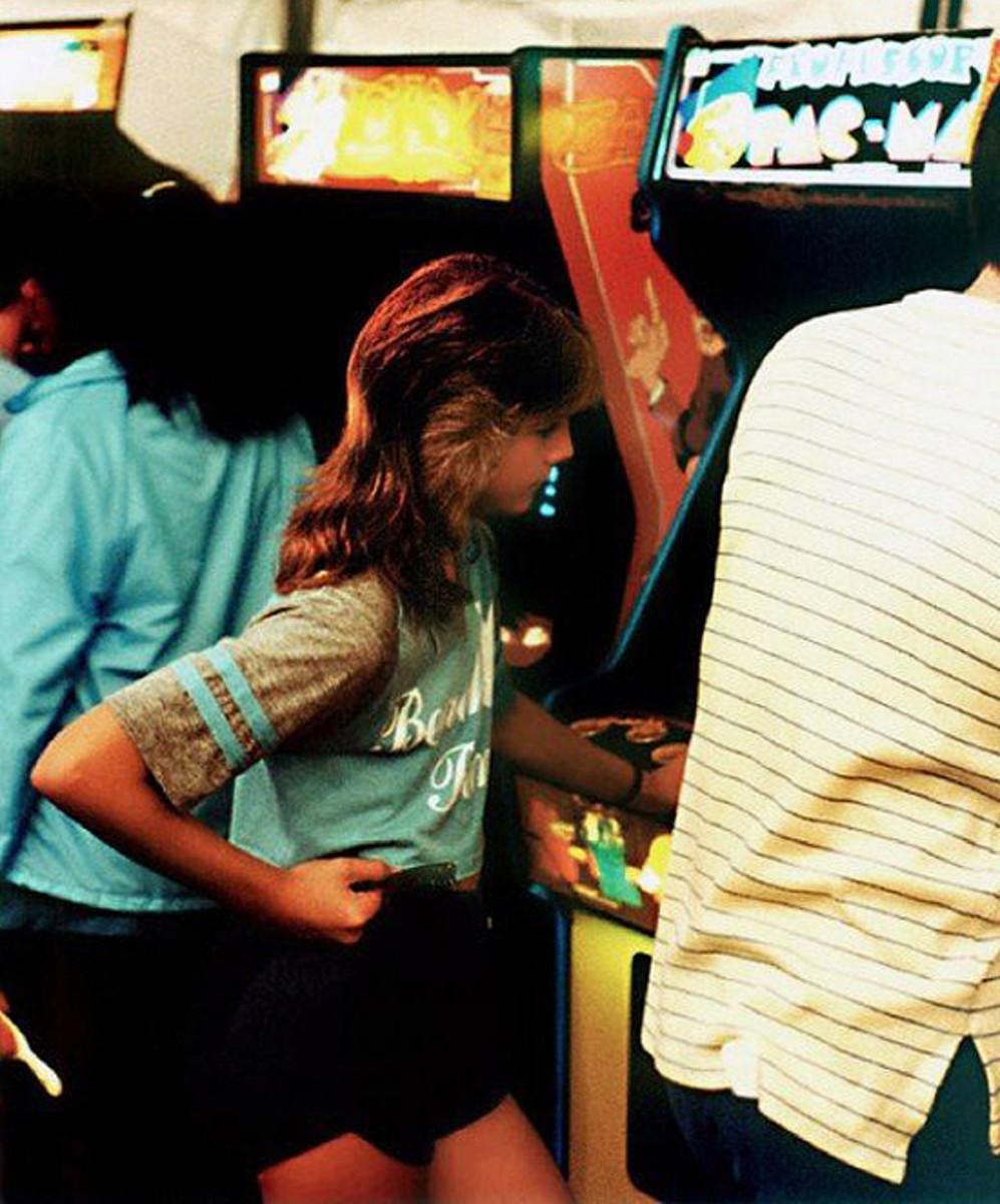 Girl in an arcade, 1980s.