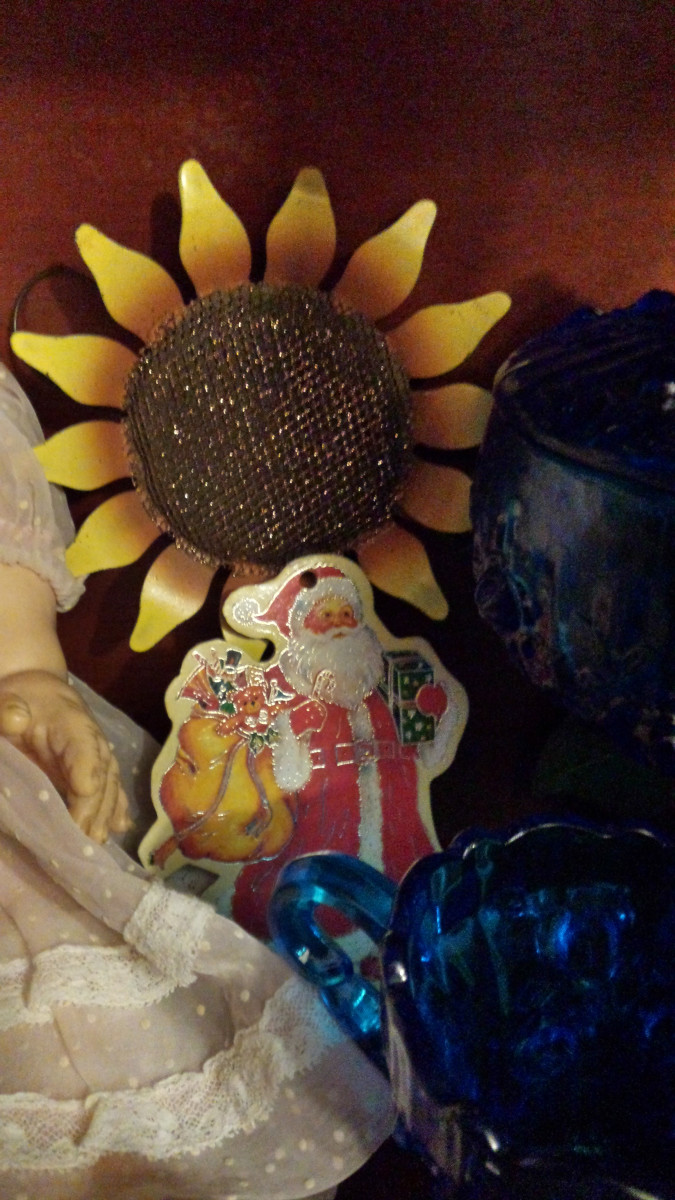 Photograph of vintage cardboard cutout Santa ornament with gold outlines.  He stands in front of a metal sunflower and beside antique blue glass.  There is a baby doll seen only in part on the photo's left side.
