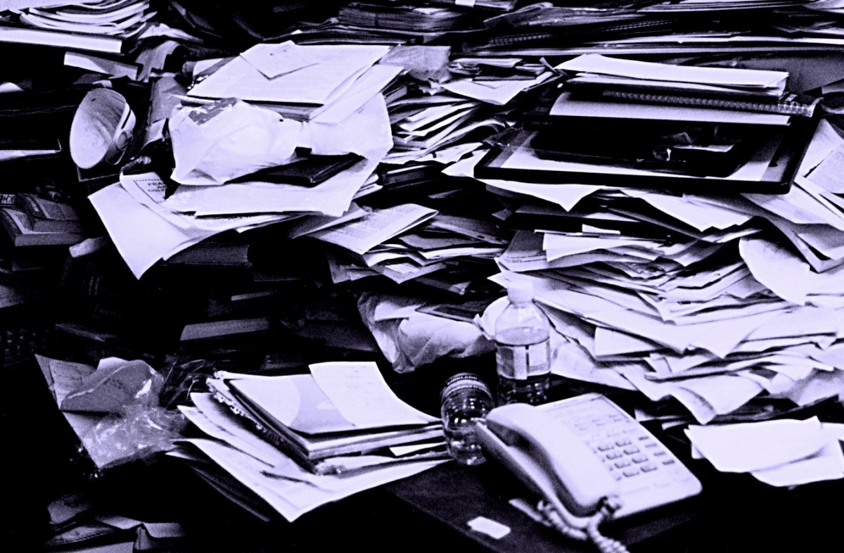 Piles of paperwork are overwhelming, leading to procrastination.