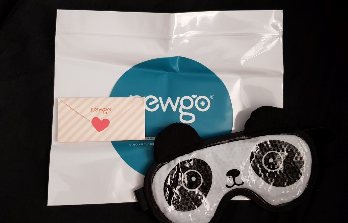 The items inside the packaging of the Newgo hot and cold therapy gel eye mask. A panda eye mask, a freezer safe sealing bag to store the mask in, a sweet note from the manufacturer.