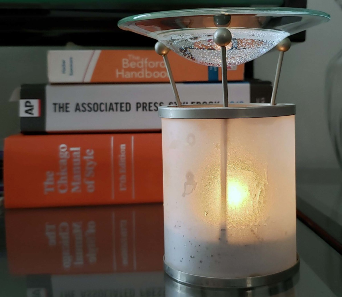 A candle-powered essential oil burner with writing reference books in the background.