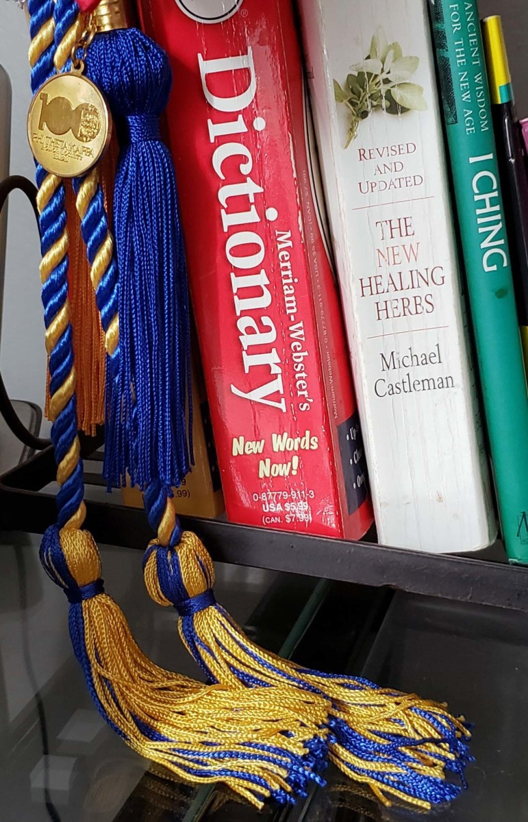 Honors cords from two of my degrees, along with an old dictionary from a primary school teacher, an herbal text, and a copy of the I Ching.