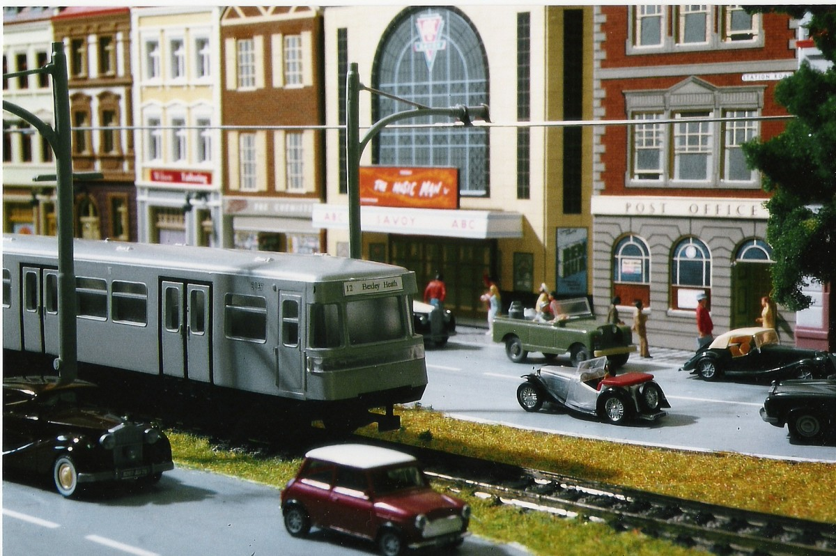 Model railway track and city setting—train amidst city traffic and buildings.