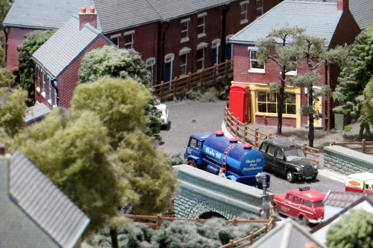 A model train community with buildings,cars, and landscaping.