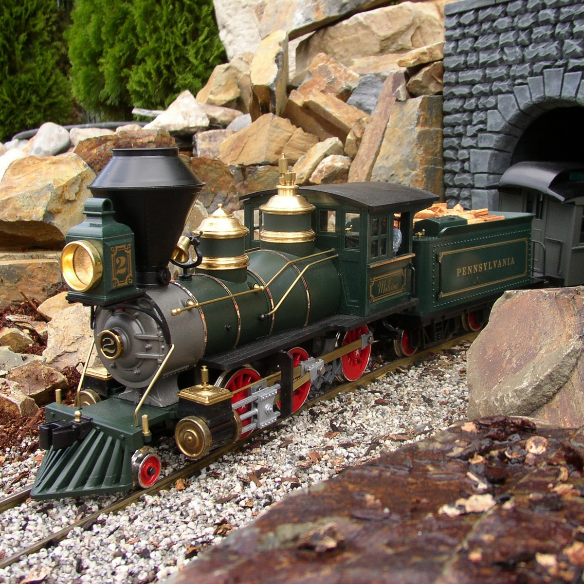 A model scale locomotive emerging from a stone mountain passage.