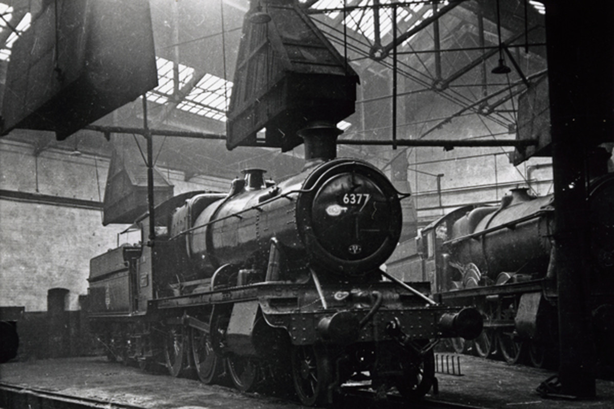Taunton, mid-Somerset had a GWR shed, code 83B. Here, looking spick and span, a GW 43XX tender loco class 2-6-0 rests under the smoke extractor