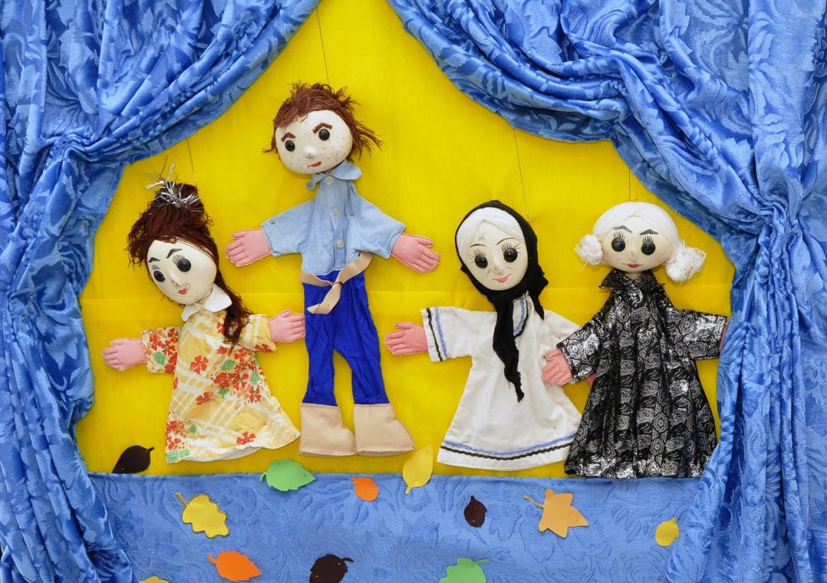 A cast of simple single-string puppets on a stage.