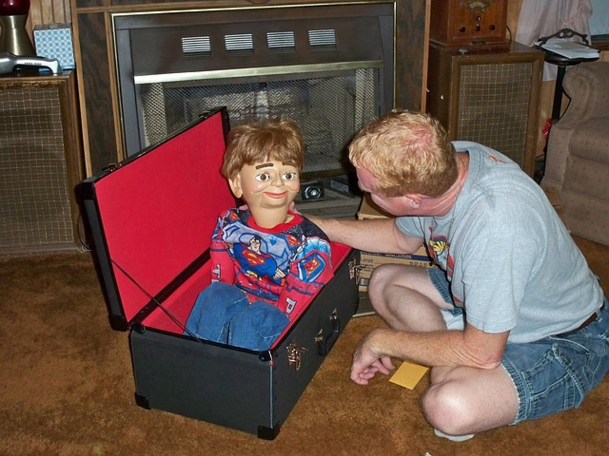 A ventriloquist preparing for his night gig by removing his Superhero dummy from his trunk.