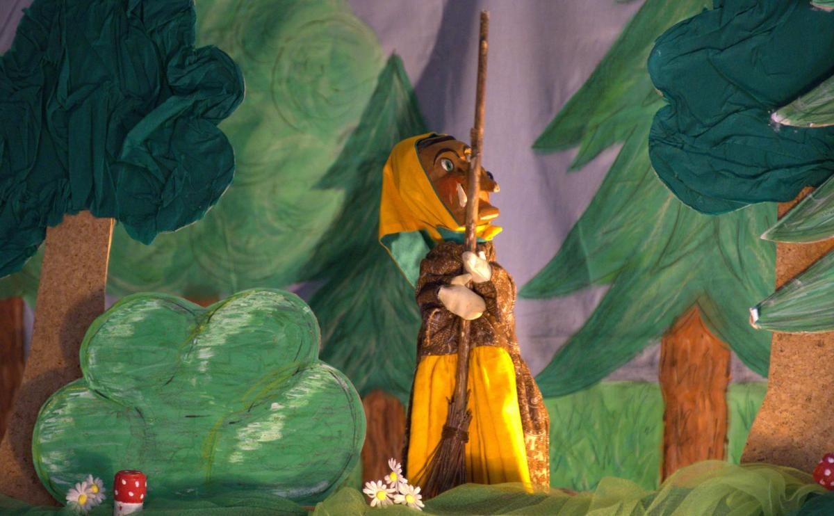 A paper-mache witch performing on stage.