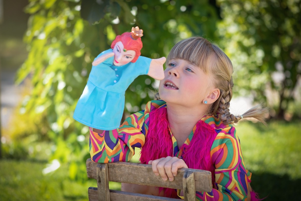 A child working her hand puppet.