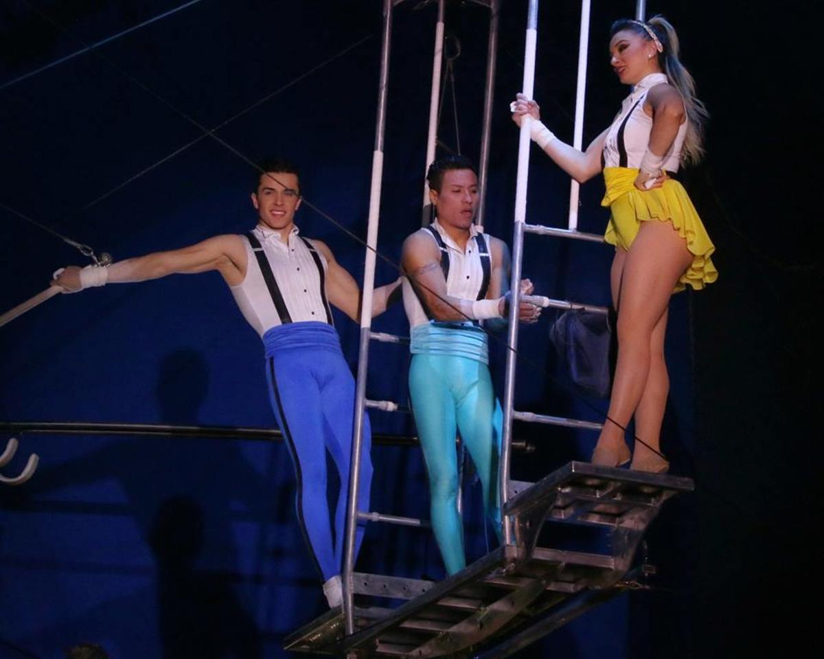 As he prepares to take the bar, Mauricio Navas (center) pats the fabric bag containing smooth, white chalk; Big Apple Circus