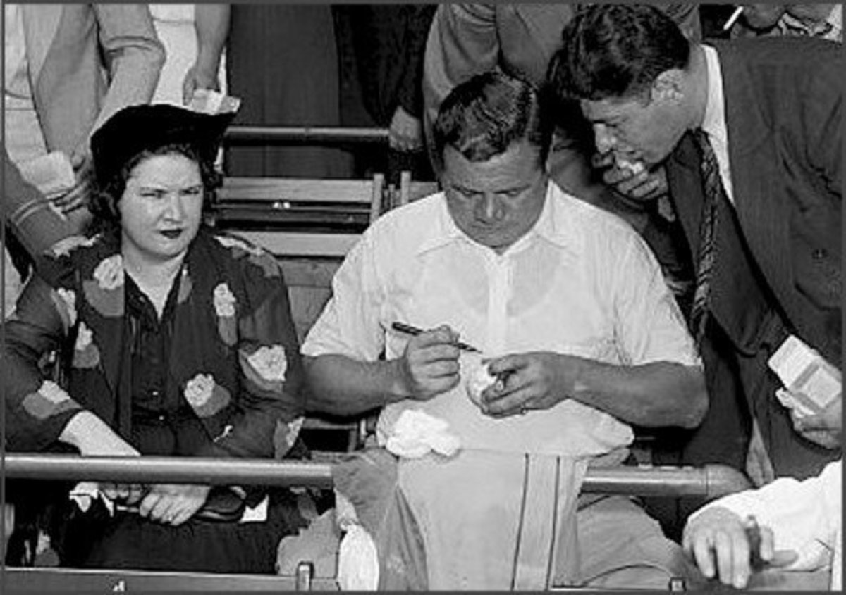 That's Babe Ruth's wife Claire next to him while he obligingly signs a fan's baseball.  She sometimes signed his through-the-mail autograph requests and did a pretty good job of mimicking his signature.