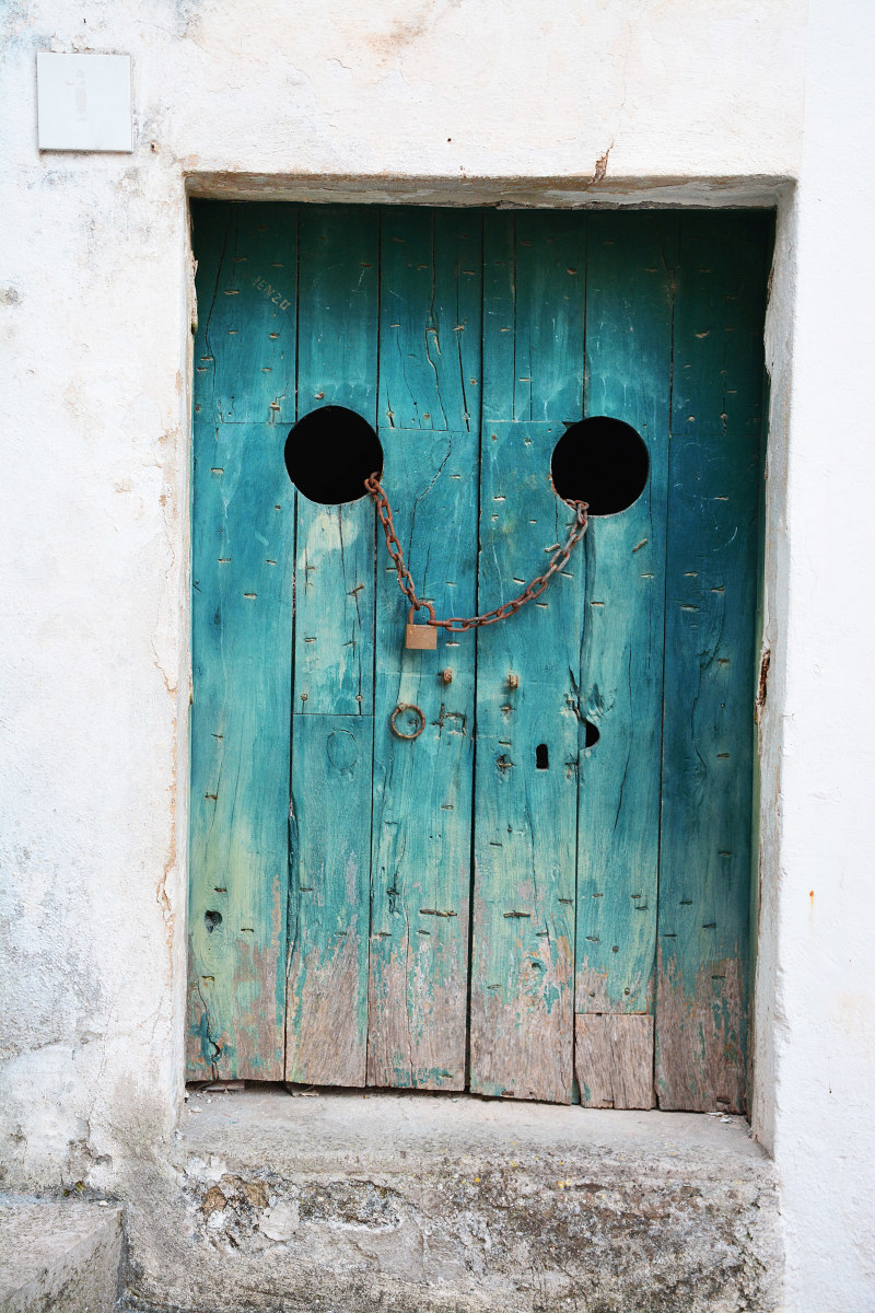 A bright teal door set in a white building. It's locked with a chain going through the doors, and the paint is worn off near the bottom. What could be on the other side?