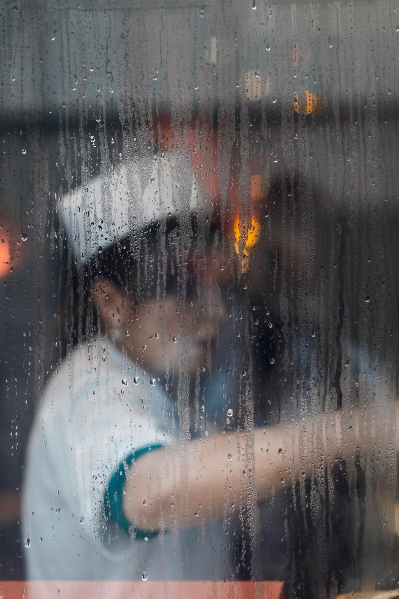 A woman at work, wearing a uniform and a white hat behind a foggy, rainy window. What's her story?
