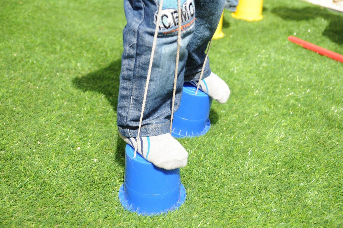 Children enjoy walking on cans or hand-held homemade wooden stilts.