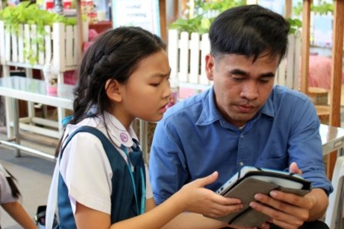 A teacher checks the work of a student on a tablet computer