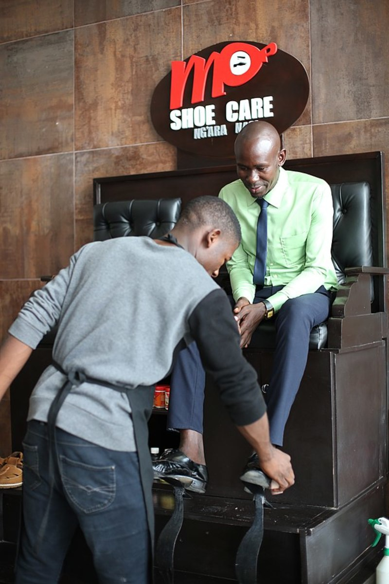 A shoe shine man is working at his firm-Mlimani city Mall, Dares salaam.
